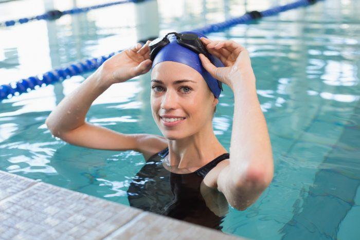 Женщина снимает очки для плавания в бассейне