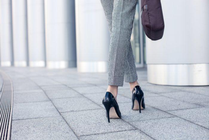 Женские ноги в клетчатых штанах и черных туфлях на каблуке