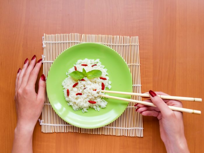 Женские руки держат палочки над зеленой тарелкой с рисом