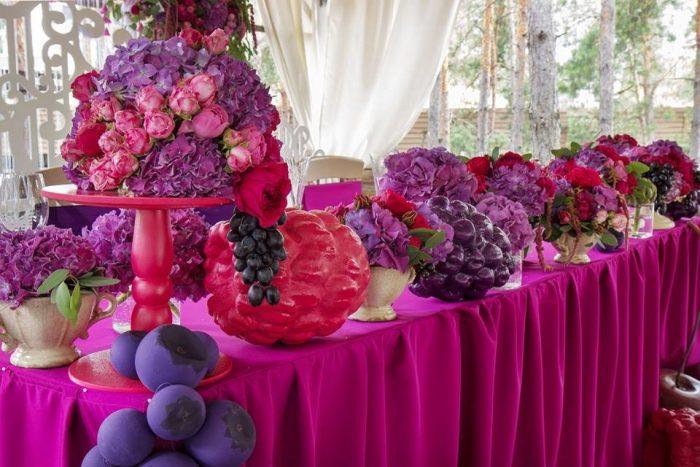Живые цветы и искусственные ягоды на столе с розовой скатертью