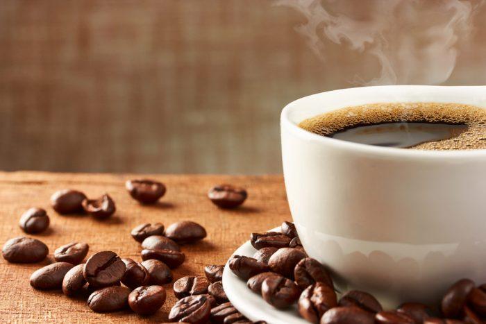 Белая чашка с кофе на столе в кофейных зернах