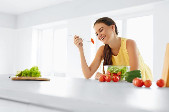 Девушка обедает салатом на кухне