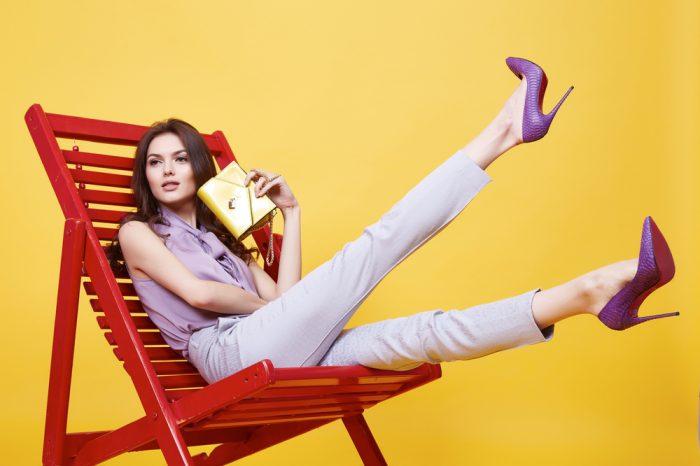 Девушка сидит на красном стуле на желтом фоне