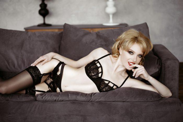 Девушка в черном белье лежит на диване