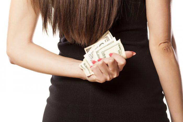 Девушка держит за спиной деньги