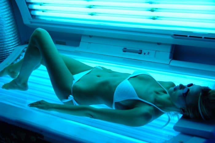 Девушка в белом купальнике лежит в солярии