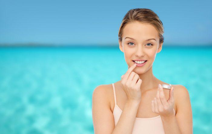 Девушка наносит бальзам на губы на фоне воды
