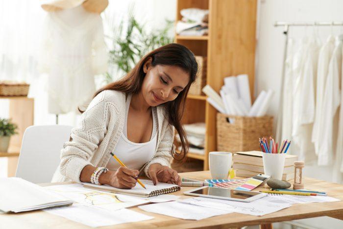 Женщина рисует дизайн одежды