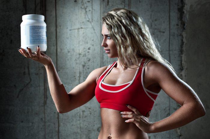 Девушка в красном топе с банкой спортивного питания