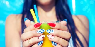 Девушка с летним маникюром держит стакан сока с соломкой