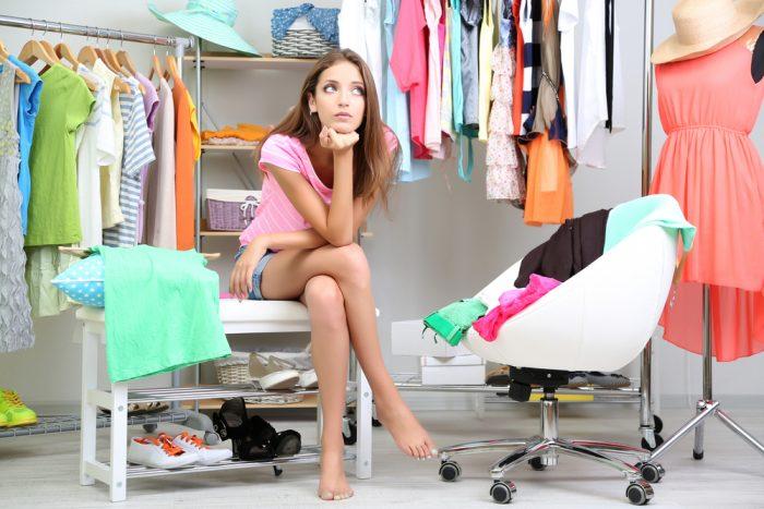 Девушка сидит в комнате среди вещей и задумалась