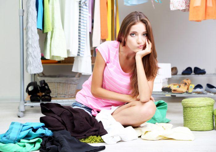 Девушка сидит на полу в вещах