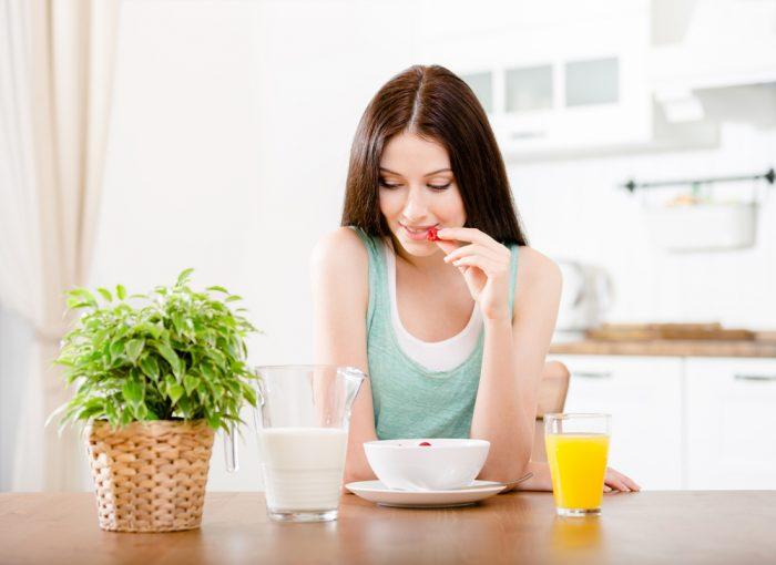 Девушка сидит за столом перед тарелкой, молоком и соком