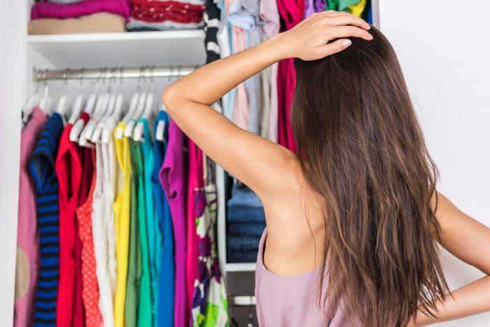 Девушка держится за голову и смотрит на шкаф и вещами