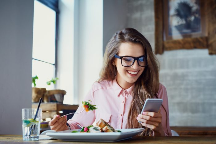 девушка смотрит в телефон и кушает салат
