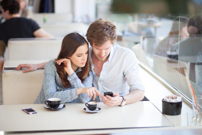 Девушка сммотрит в телефон парня в кафе