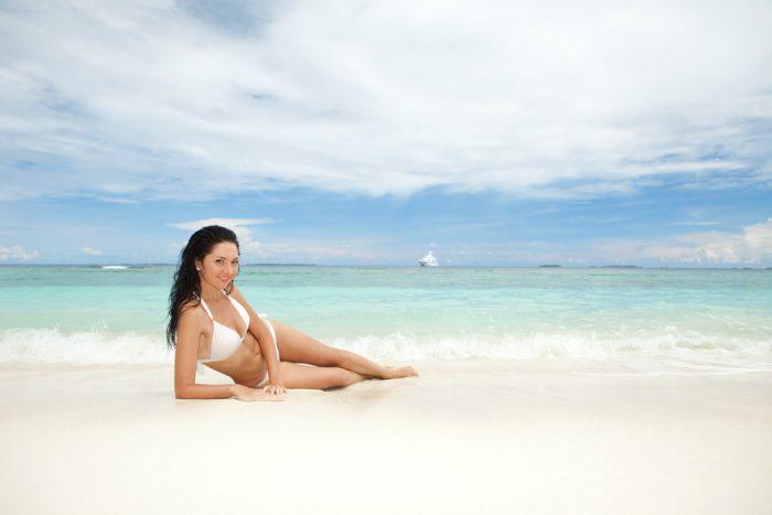 Девушка в белом купальнике лежит у моря