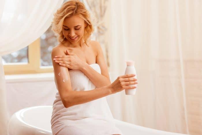 девушка в белом полотенце наносит крем на плече Yuriy Rudyy