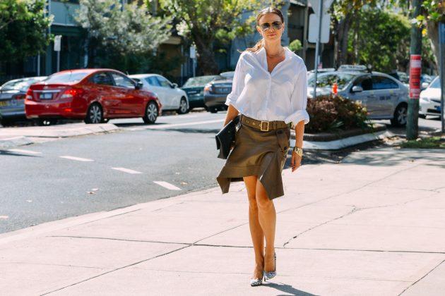 Девушка идет по улице в белой блузке и кожаной юбке