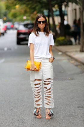 Девушка в белой футболке и белых брюках с разрезами