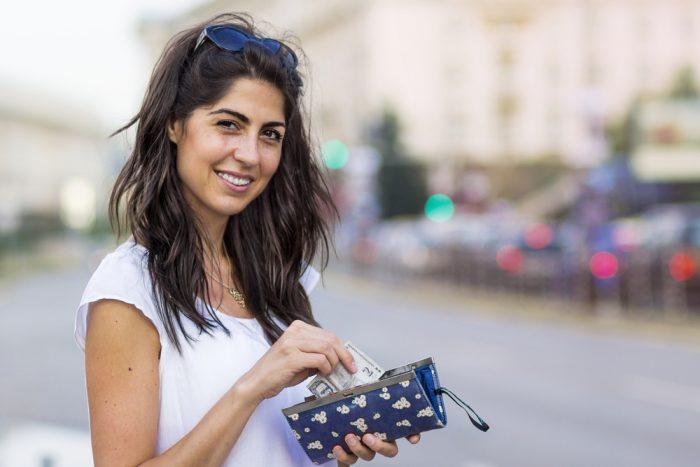 Девушка в белой футболке ложит деньги в кошелек