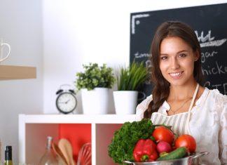 Девушка в белой кофте с овощами на кухне