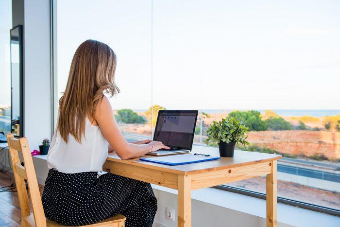 Девушка в бело майке и черных брюках сидит за столом с ноутбуком