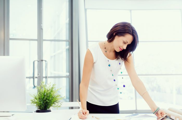 Девушка в белой кофте с бусами делает запись стоя