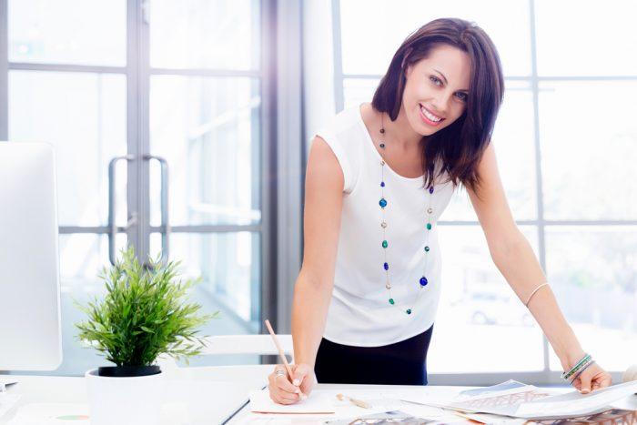 Девушка в белой кофте с бусами улыбается и делает запись