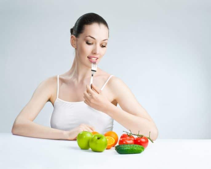 Девушка в белой майке за столом перед овощами и фруктами