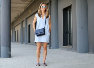 девушка в голубом коротком платье с черной сумкой