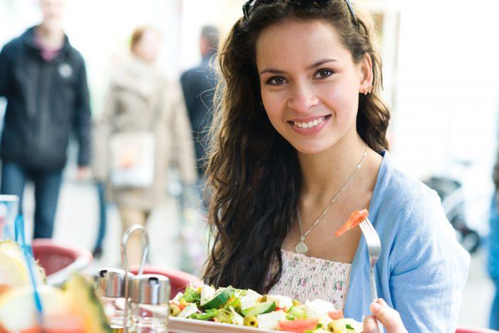 девушка в голубой кофте ест салат в кафе
