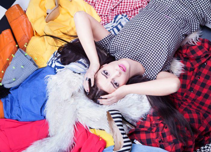 Девушка лежит на одежде и обуви