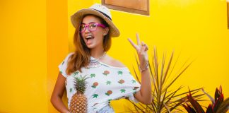 Девушка в коротких шортах с ананасом в руках