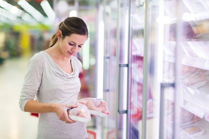 Девушка в магазине выбирает курицу