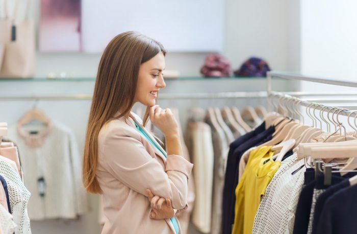девушка в магазине смотрит на одежду