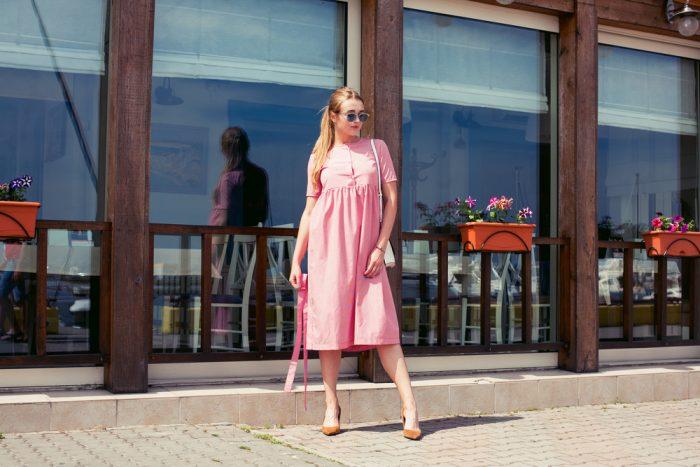 Девушка в розовом платье на фоне кафе