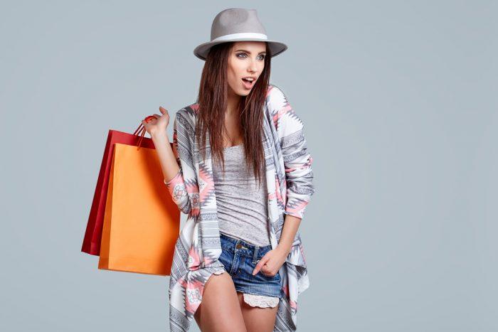 Девушка в серой майке и в серой шляпе с покупками