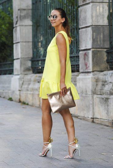 Девушка в коротком желтом платье и с золотым клатчем