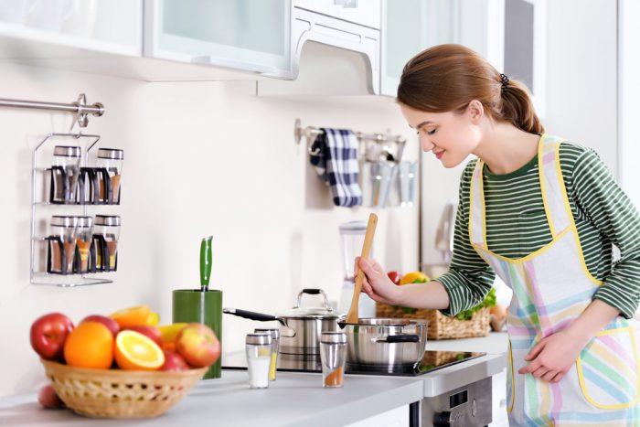 Девушка варит на кухне суп