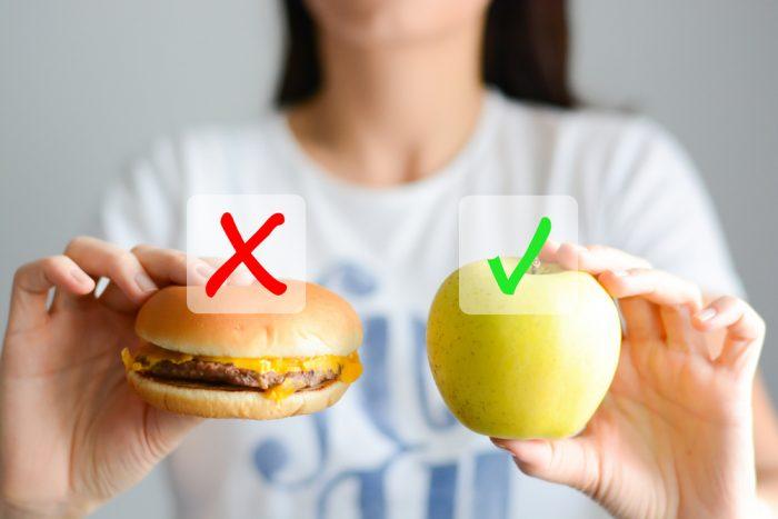 Девушка с гамбургером и яблоком в руке