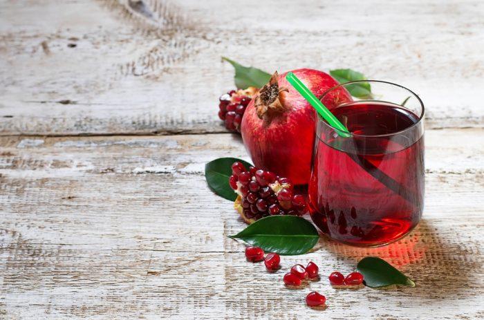 Гранатовый сок в стакане с соломкой возле граната