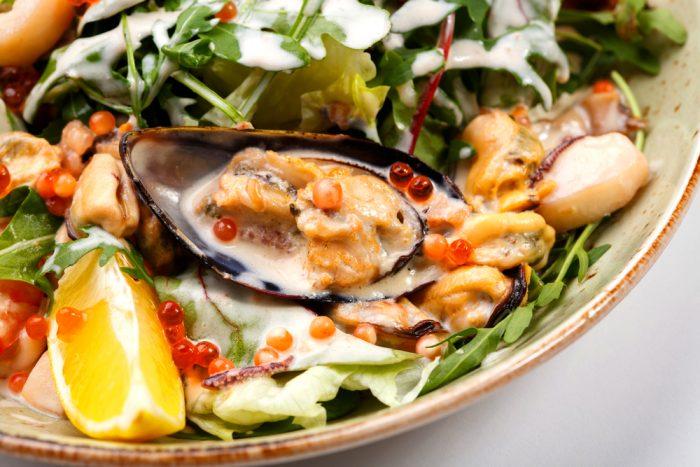 Икра и различные морепродукты с долькой апельсина на тарелке