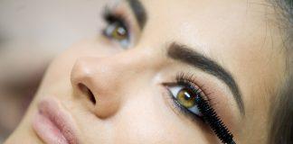Кисточка туши возле глаза девушки