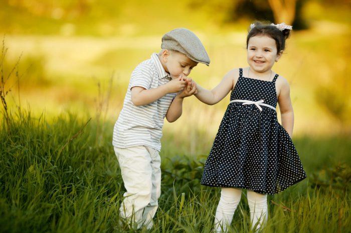 Мальчик целует руку девочке в платьице в горошек