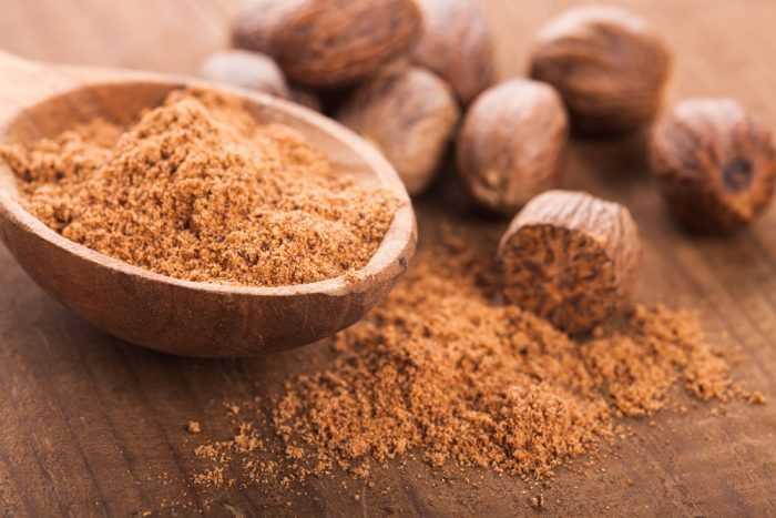Мускатный орех на деревянном столе с тарелочкой молотого