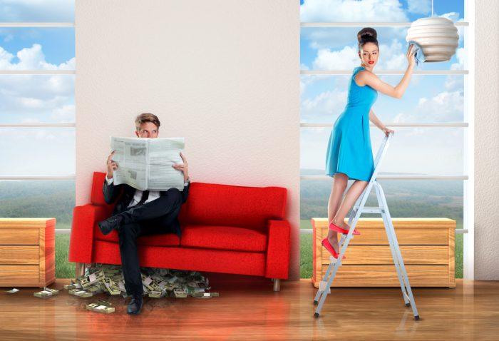 Муж сидит на диване с деньгами возле убирающей жены
