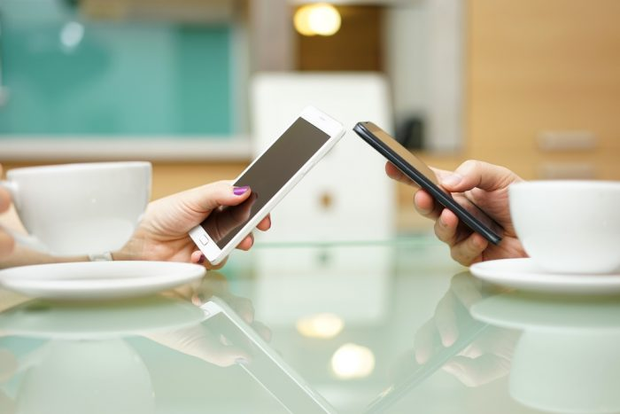 Мужская и женская рука с телефонами