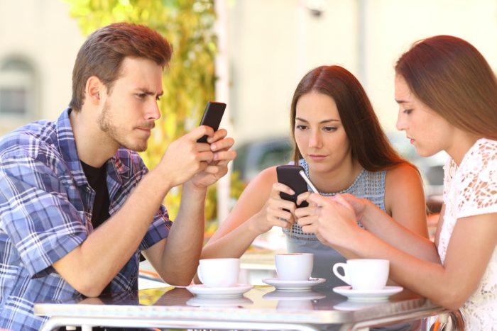 Парень с двумя девушками в кафе смотрят в телефоны