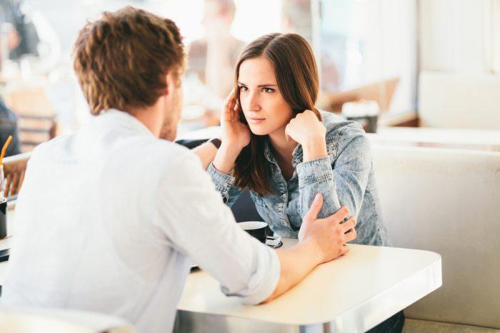 Девушка сидит в кафе с парнем в белой рубашке